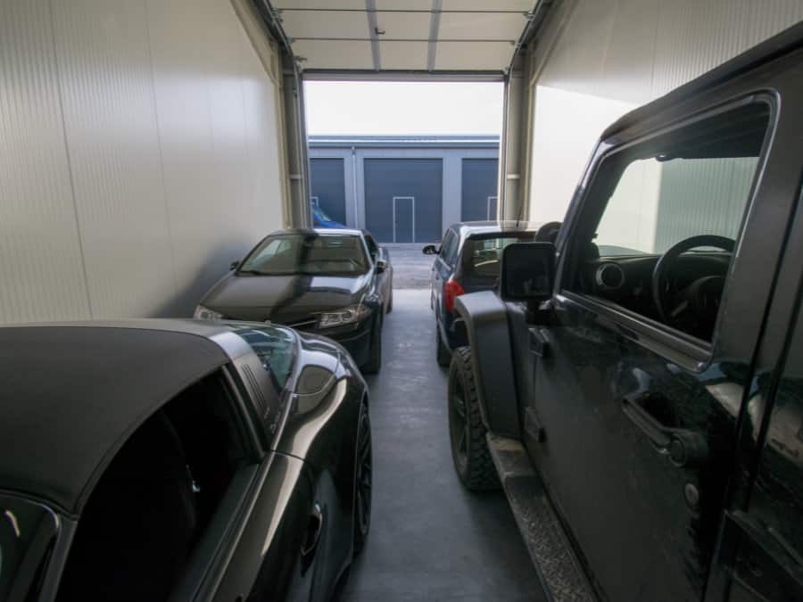 Innenansicht einer Lagerhalle mit vier PKWs